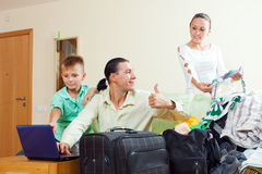 Family of three choosing resort and packing suitcases Royalty Free Stock Images