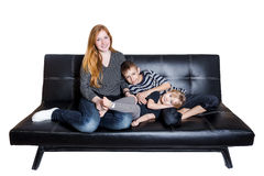 Family of three at the couch isolated on white background Royalty Free Stock Photography