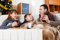 Family of three with cups of tea  in Christmas Royalty Free Stock Photography