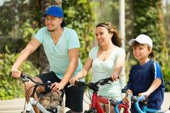 Family of three cycling across city Royalty Free Stock Photos