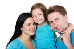 Family of three, daughter hugs her parents. Family of three in blue shirts, little daughter hugs her parents Stock Images