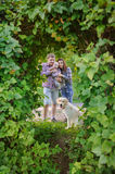 Family of three with a dog in the park, mother and father holding a child. Happy parents father, mother, their child and their dog on a walk in the park. Dog Royalty Free Stock Photos