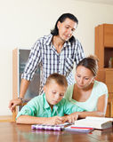 Family of three doing homework in home interior Stock Photos