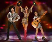 Disco family perform on stage. A family of three dressed in disco style perform on stage in the spotlight royalty free stock photos