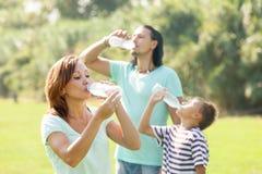 Family of three drinking water Royalty Free Stock Photos