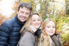 Family of three enjoy autumn park having fun smile. And happy royalty free stock photography