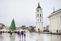 Family of three enjoying their time by the Christmas tree in Vilnius, Lithuania Royalty Free Stock Photos