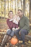 Family of Three in the Forest. A family of three in the forest in the fall.  A mother wearing a plum colored sweater and blue jeans.  Dad is wearing a green Royalty Free Stock Photography