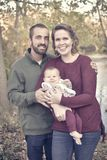 Family of Three by the River in the Fall. A family of three in the forest in the fall.  A mother wearing a plum colored sweater and blue jeans.  Dad is wearing a Stock Photo
