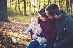 Family of Three in the Forest. A family of three in the forest in the fall.  A mother wearing a plum colored sweater and blue jeans.  Dad is wearing a green Stock Images