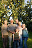 Family of three generations arm in arm in orchard, smiling, portrait Stock Images