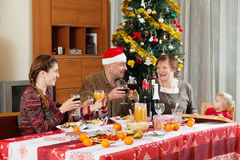 Family of three generations celebrating New Year. Over celebratory table at home Stock Image
