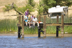Family of three generations fishing from jetty, motor home in background, low angle view Stock Image