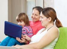 Family of three generations looks netbook Stock Photos