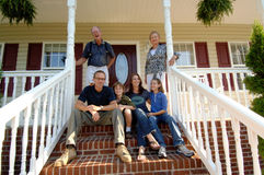 Family of three generations on porch. A happy extended family of grandparents, parents and children on the steps of a front porch Royalty Free Stock Photography