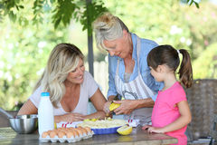 Family of three generations preparing apple pie. Grandmother, mother and daughter preparing apple pie Royalty Free Stock Photography