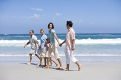 Family of three generations walking on beach, holding hands stock images
