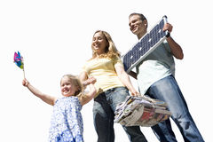 Family of three, girl with pinwheel, father with solar panel, mother with bundle of newspapers, cut out Royalty Free Stock Images