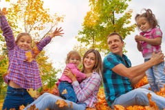 Family with three girls in autumn leaves. Happy family in the autumn park sitting in the orange maple leaves and girl throws them Royalty Free Stock Photography