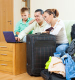 Family of three  going on holiday. Ordinary family of three with luggage choosing the tickets in internet and going on holiday Royalty Free Stock Photo