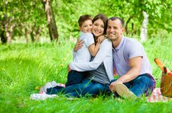 Family of three has picnic in park. Concept of happy family relations and carefree leisure time stock photography