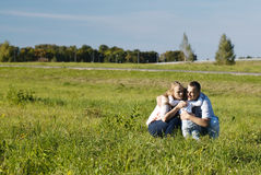 Family of three having fun outdoors Stock Images
