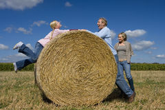 Family of three by hay bale in field, father playing with daughter (11-13) Stock Photos