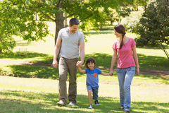 Family of three holding hands and walking at park Stock Photography