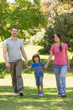 Family of three holding hands and walking at park Stock Images
