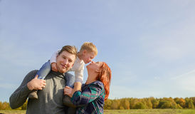 Family of three huging and kissing. On the sky background royalty free stock photo