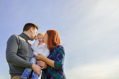 Family of three huging and kissing. On the sky background stock image