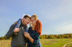 Family of three huging and kissing. On the sky background royalty free stock images