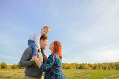 Family of three huging and kissing. On the sky background stock photo