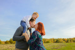 Family of three huging and kissing. On the sky background stock photography