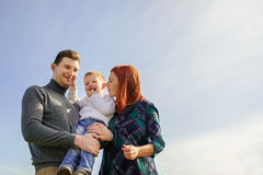 Family of three huging. The sky background royalty free stock images