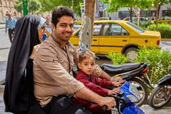 A family of three Iranians is riding motorbike, Isfahan, Iran. Isfahan, Iran - April 24, 2017: An Iranian family of three people moves around the city using a stock images