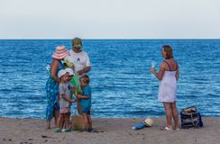 Family with three kids on the beach. One big family are enjoying their time on the seaside. The children are grumpy because they have to leave the beach The Royalty Free Stock Photography
