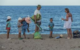 Family with three kids on the beach. One big family are enjoying their time on the seaside. The children are grumpy because they have to leave the beach The Stock Photography