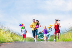Family with three kids. Running down a hill in summer Stock Photography