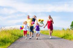 Family with three kids running stock photo