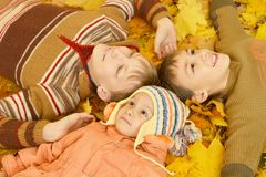 Family of three lying on yellow leaves Stock Photos