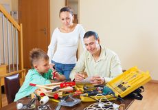 Family of three modeling something. Family of three with teenager modeling something with the working tools Stock Photo