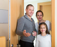 Family of three opening door of new apartment Stock Photography