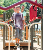 Family of three overcomes the obstacle course. On the playground in summer Stock Photos