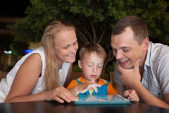 Family of three with pad in outdoor cafe Royalty Free Stock Photos