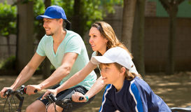Family of three in the park with bicycles. Sports family of three  relaxing in the park with bicycles Royalty Free Stock Photos