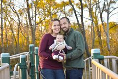 Family of Three at the Park in the Fall. A family of three at the Park in the fall. A mother wearing a plum colored sweater and blue jeans. Dad is wearing a Stock Photography