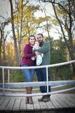 Family of Three at the Park in the Fall. A family of three at the Park in the fall. A mother wearing a plum colored sweater and blue jeans. Dad is wearing a Royalty Free Stock Photo