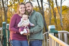 Family of Three at the Park in the Fall. A family of three at the Park in the fall. A mother wearing a plum colored sweater and blue jeans. Dad is wearing a Stock Photo