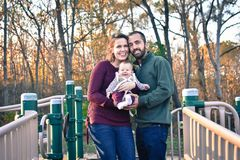 Family of Three at the Park in the Fall. A family of three at the Park in the fall. A mother wearing a plum colored sweater and blue jeans. Dad is wearing a Royalty Free Stock Photography